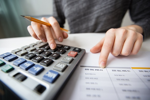 Closeup of Accountant Hands Counting on Calculator